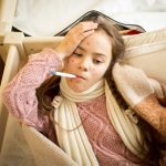 sick girl with chickenpox lying in bed and measuring temperature